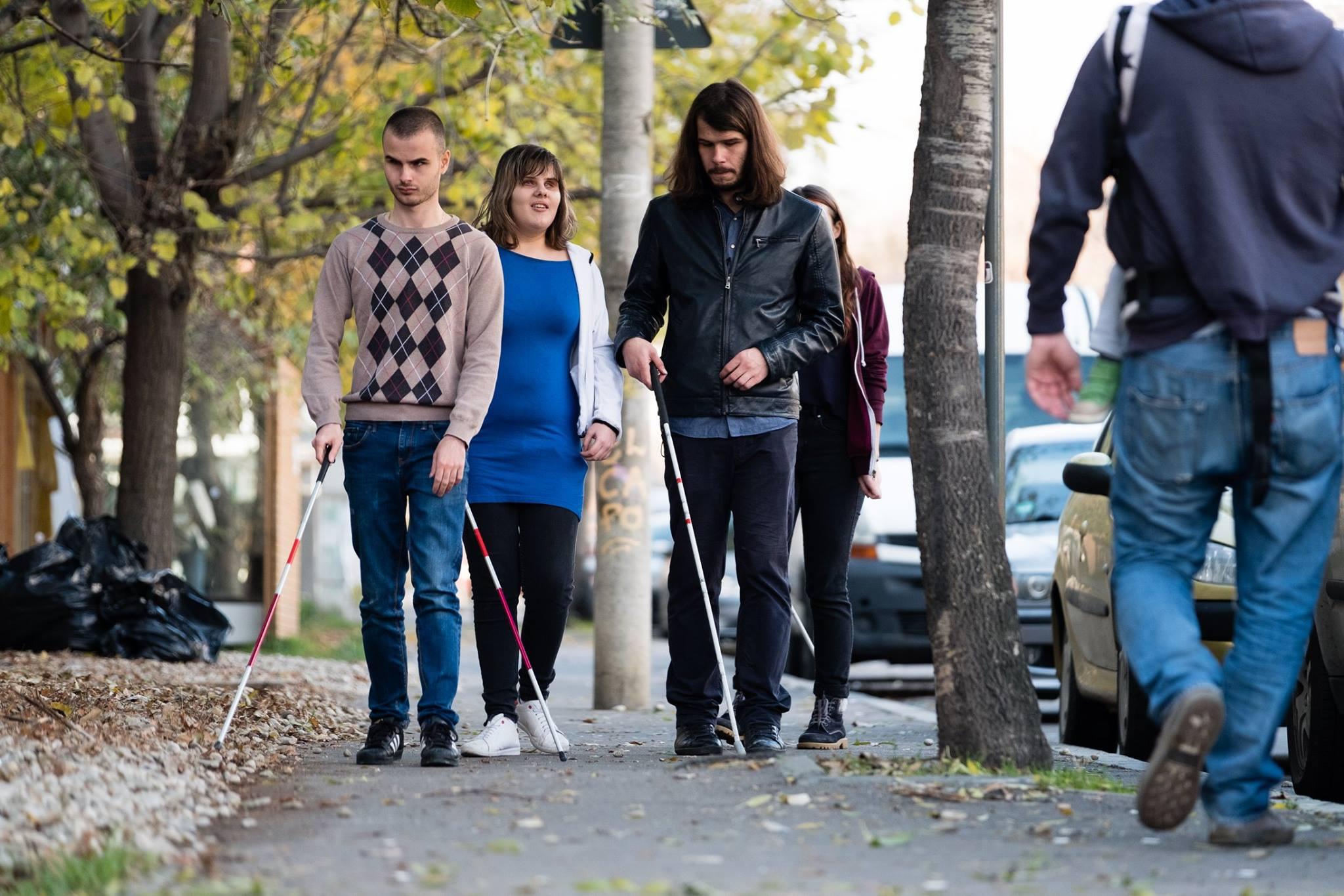 Descriere foto: grup de participanti exploreaza cu bastonul spatiul din jurul LFI.