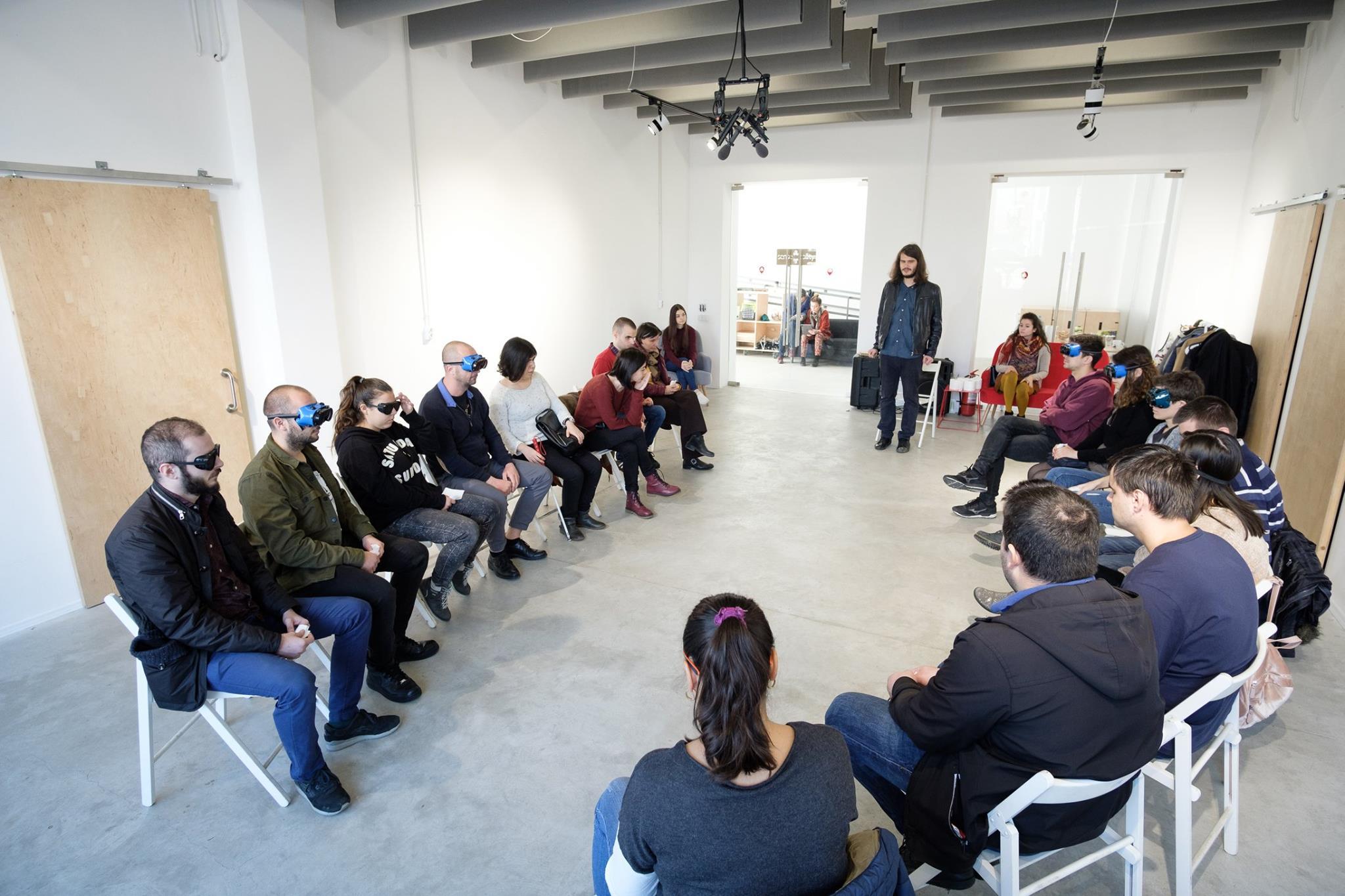 Descriere foto: participantii asezati pe scaune, in cerc, iar Alex Cucu le prezinta atelierul.