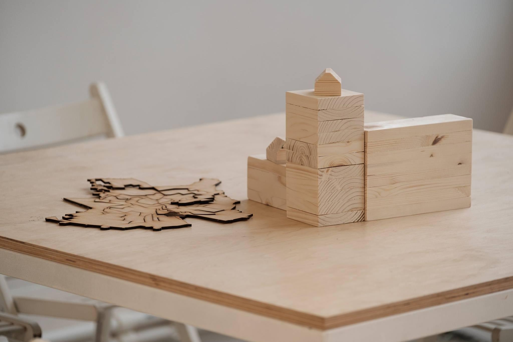 Descriere foto: machetele si elementele din lemn asezate pe masa, la inceputul atelierului.