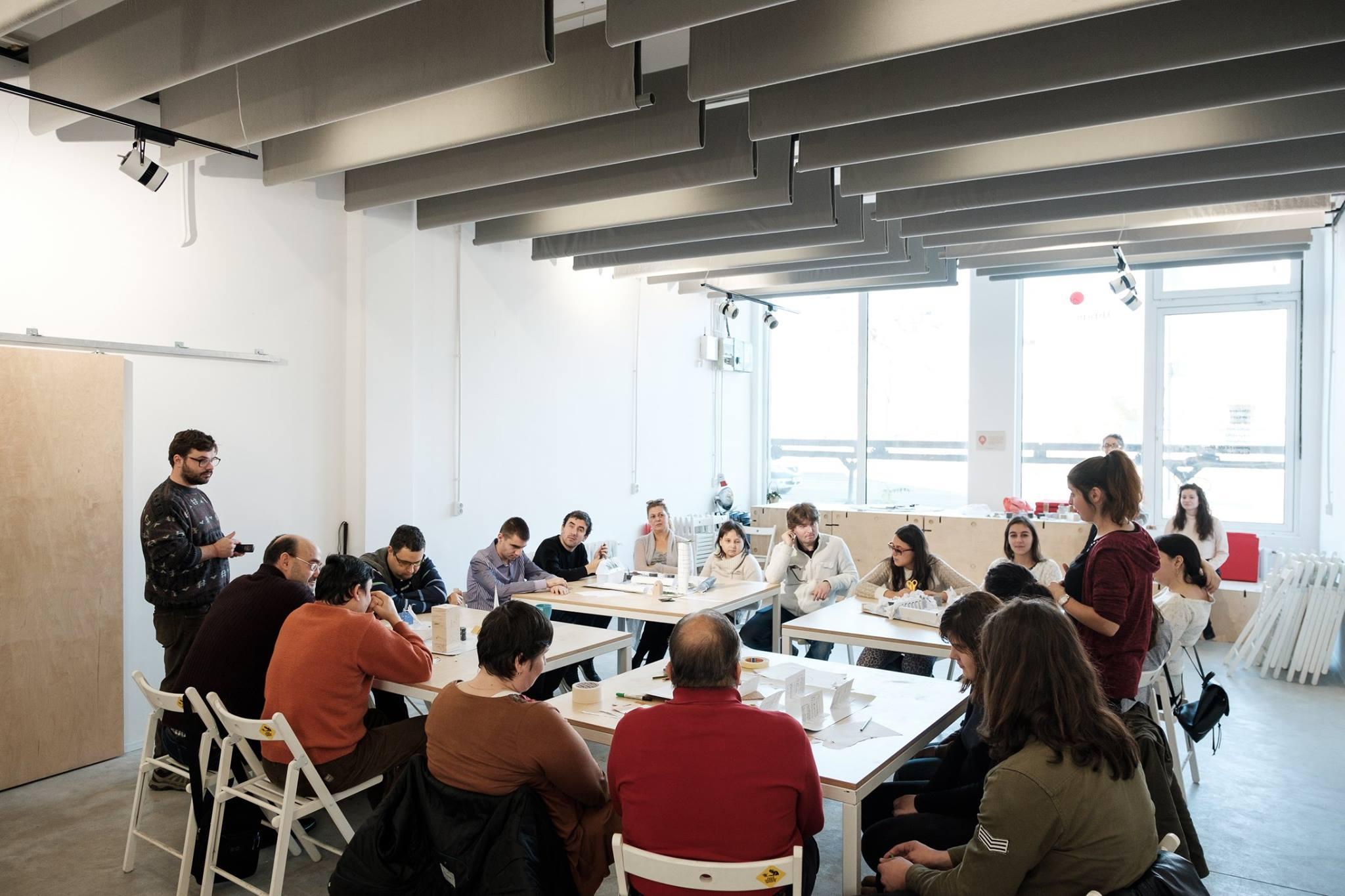 Descriere foto: participantii asezati la mesele de lucru unde fiecare echipa a creat orasul ideal.